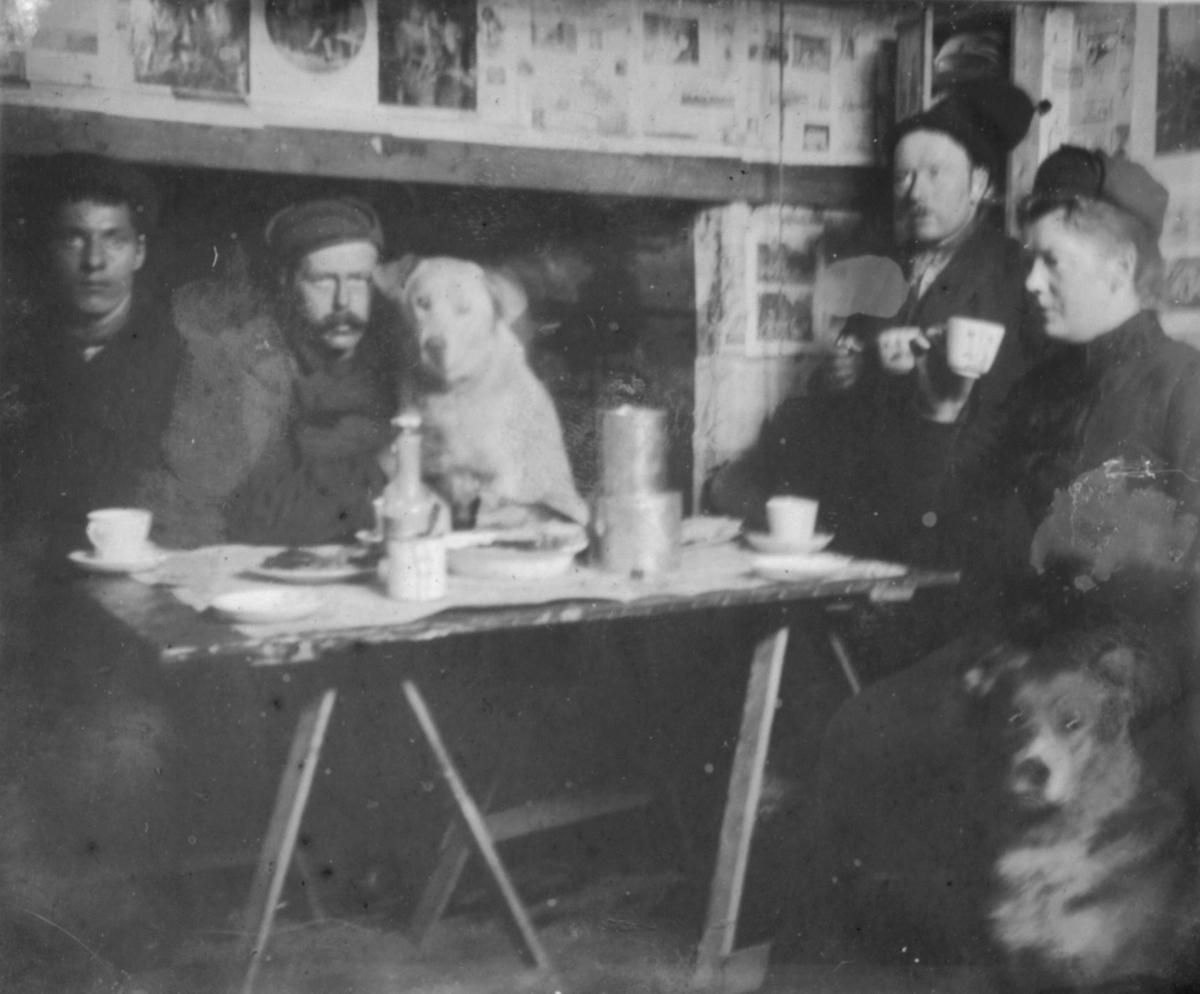 På tur til Blåsenberg våren 1903. Fire menn og to hunder sitter ved et bord. Det er kaffekopper, fat og bokser på bordet. På veggen er det plakater eller lign.
