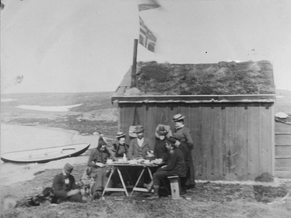 Fire menn og tre damer sitter rundt et bord utenfor en hytte. En mann står og lener seg til hytteveggen med en kopp i handa. På bordet er det kopper og fat. Det er torv på taket til hytta. Det henger også et flagg. I vannkanten ligger en robåt.