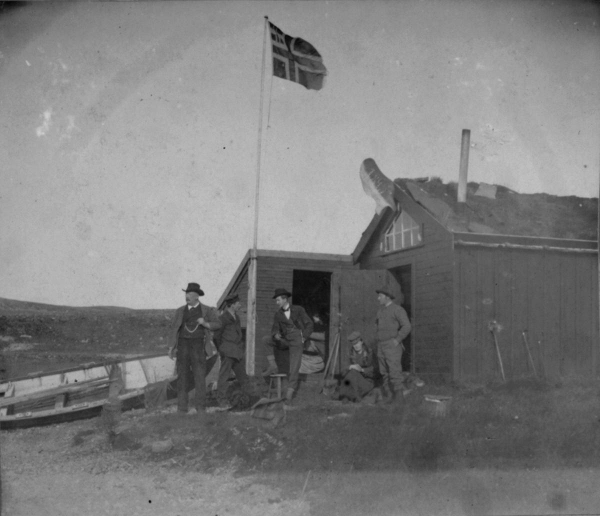 Viktor Olsen og Evensen står og snakker ved flaggstanga. Antagelig Karl Ohlsen som står til venstre.