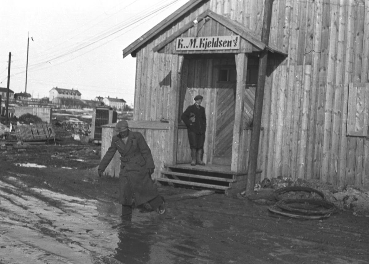 Brakke som huset K.M.Kjeldsen på Ørtangen i Vadsø. Mennene foran brakka er ukjente.
