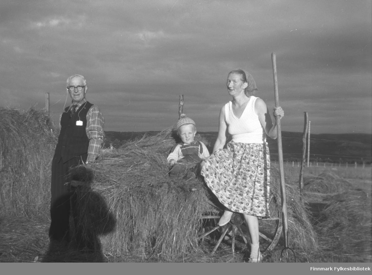 Slåttearbeid på gården Mikkelsnes, ca. 1960-1961. Fra venstre: Karl Johnsen, Asle Lindseth og Marine Smuk. De frakter høy i hus med handvogn