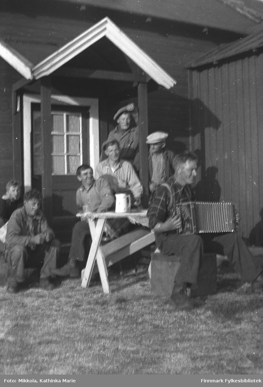 Munter gruppe menn benket rundt en kaffekanne utenfor Mikkelsnes. Mannen til høyre trakterer et trekkspill. Dette er antakelig en arbeidsgjeng, kanskje de som jobbet på veien i Neiden