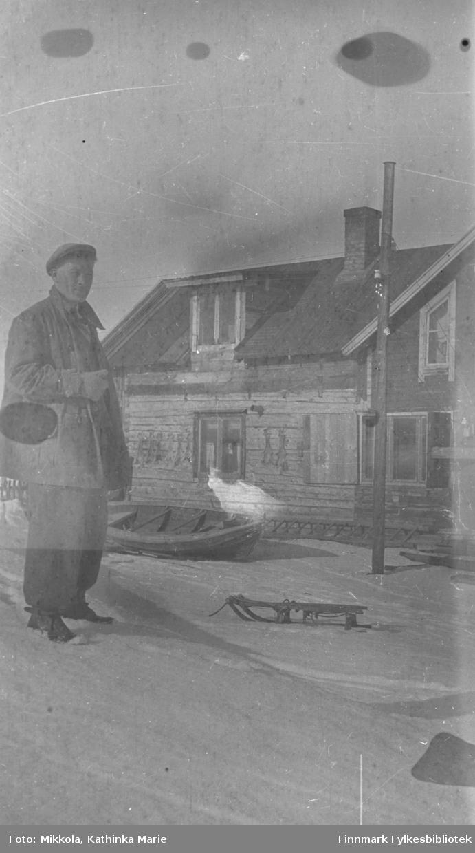 En ung mann i vinterklær, Andreas Mikkola bak våningshuset på Mikkelsnes. Han står ved en liten kjelke. I bakgrunnen en robåt trukket opp ved siden av huset. Det er sperret opp små skinn på husveggen - hareskinn?