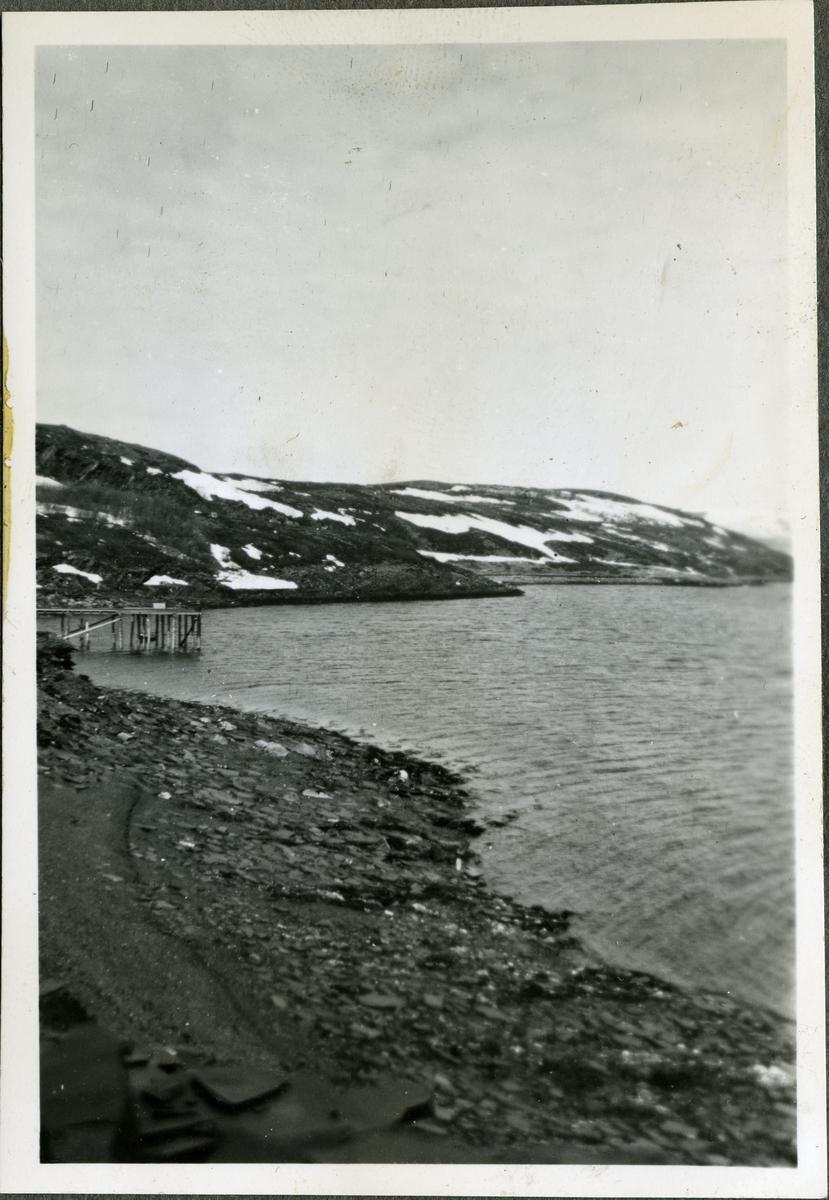 Et bilde av fjæra i Friarfjord. På bildet kan man se en liten kai, fjell og havet.