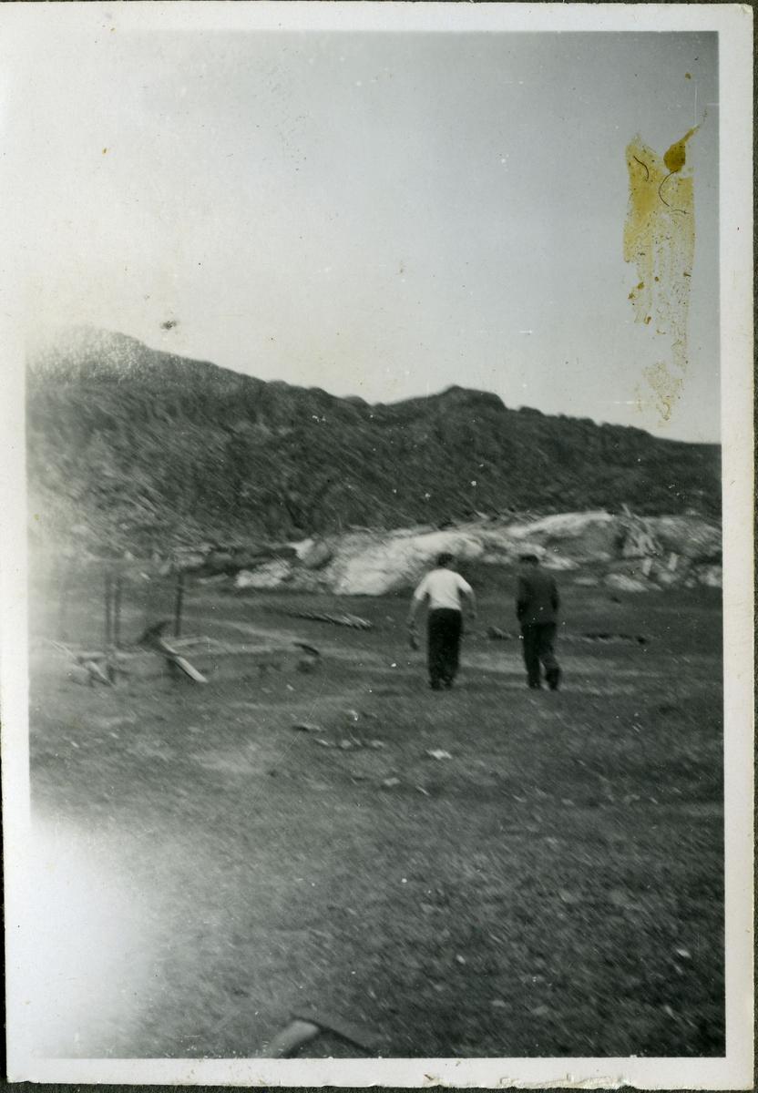 To ukjente menn går i gruvelandskapet på skiferbruddet i Friarfjord. I området kan man se steiner, redskaper og fjell. Mennene er kledd i jakke, bukse og skjorte.