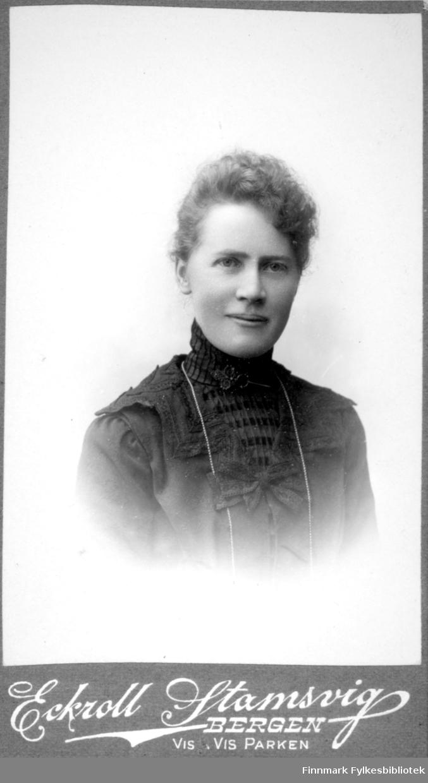 Portrett av en dame iført en mørk bluse med høy hals.