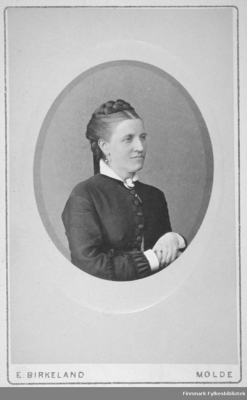 Portrett av en dame med mørk overdel på seg. Noe av den hvite blusen/skjorta ses i halsen og rundt håndleddene. Hun har øredobber og et lite smykke i halsen. Portrettet er tatt hos E. Birkeland i Molde.