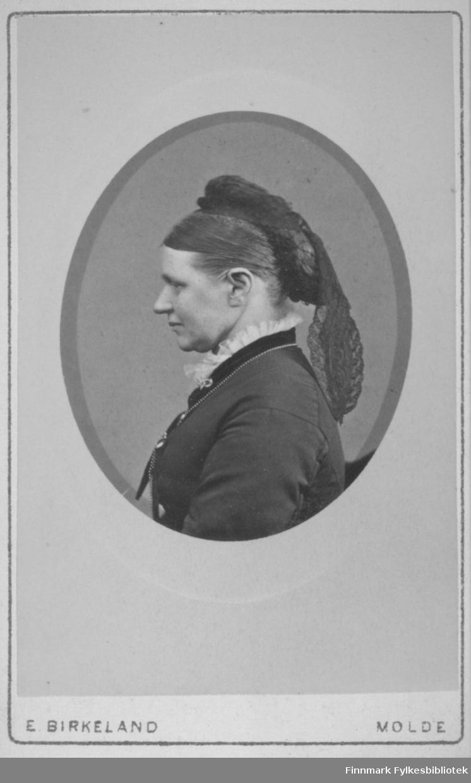 Portrett av en dame som har håret greid bakover med et tørkle over som en hestehale. Hun har en mørk jakke med et sort bånd nedenfor blondekragen. Portrettet er tatt hos E. Birkeland atelier i Molde.