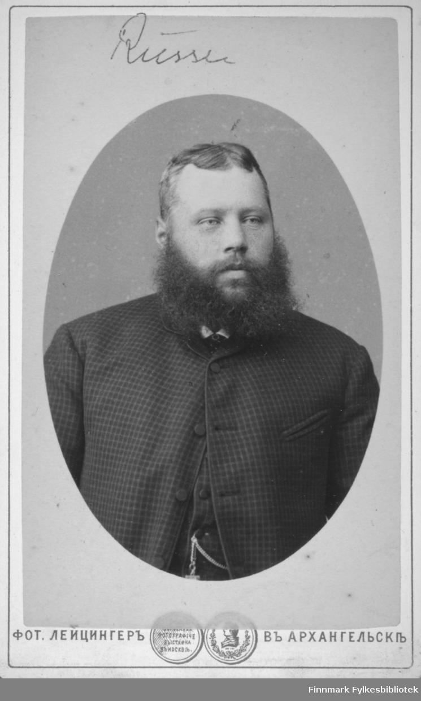 Portrett av en russisk mann med helskjegg. Han har en mørk, smårutet dressjakke på seg. Over magen henger et lommeurkjede.