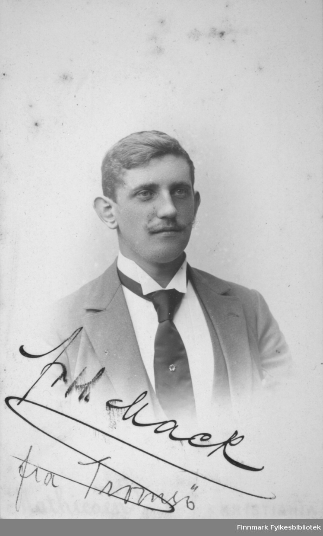 Portrett av en Mack fra Tromsø. Han har hvit skjorte med høy krage, mørk slips og noe lysere dressjakke.