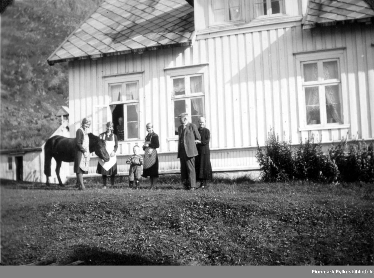 Deler av et stort, hvitt hus. Fem voksne og et lite barn poserer for bygningen. En hest står mellom de to damene som har mørke klær og hvitt forkle på. Bak barnet står en mørkkledt dame med forkle. Til venstre står en mann i finklær og sixpence på hodet. Bak han står en mørkkledt dame. Bygningen har stående panel og tre to-delte vinuer med gardiner i. Nedre del av vinduer ses oppe i arken. Bygningen har skifer på taket og en mindre bygning ses såvidt helt til venstre. Bak det igjen ses en liten del av fjellsiden. En velstelt gressplen foran huset og noen forholdsvis høye planter står inntil grunnmuren.
