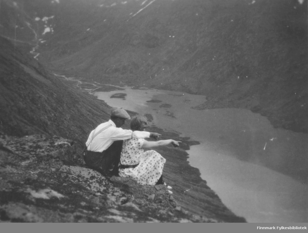 To personer sitter langt oppe i en fjellside og ser utover en lang og smal fjord. Mannen har mørk bukse, hvit skjorte, bukseseler, ermestrikk og sixpence på hodet. Damen har mønstret kjole med korte ermer og et sort belte. Det er høye og ganske bratte fjellsider og bak personene er det steiner og litt lyng på bakken. Innerst i fjorden renner en elv og noen snøflekker ligger høyt oppe i fjellet. Noen holmer og skjær ses i fjorden.