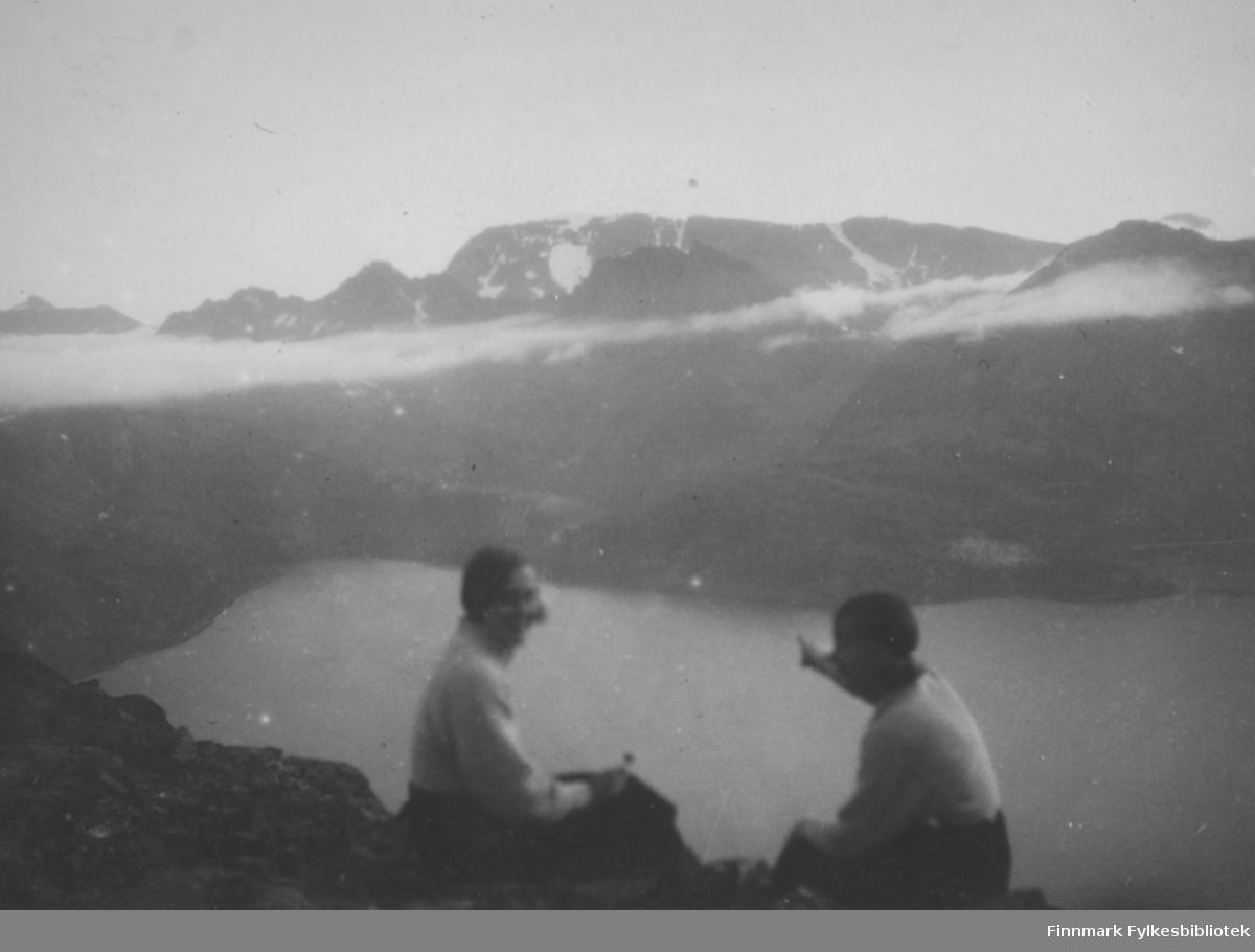 To personer sitter på en fjelltopp og ser utover en fjord. Damen til venstre har mørk bukse og en tynn, lys genser på seg. Mannen til høyre har også en mørk bukse og en tynn, lys genser. Han peker mot noe lengre inn i fjorden. Høye fjell med ganske bratte fjellsider. Noen lave, tynne skyer går på tvers av bildet. Et enda høyere fjell i bakgrunnen med noen is-/snøflekker på toppen. Et par, litt mindre topper ses mot den bakerste fjellveggen. Et nes stikker ut i fjorden helt til høyre og er med på å danne en liten bukt/vik.