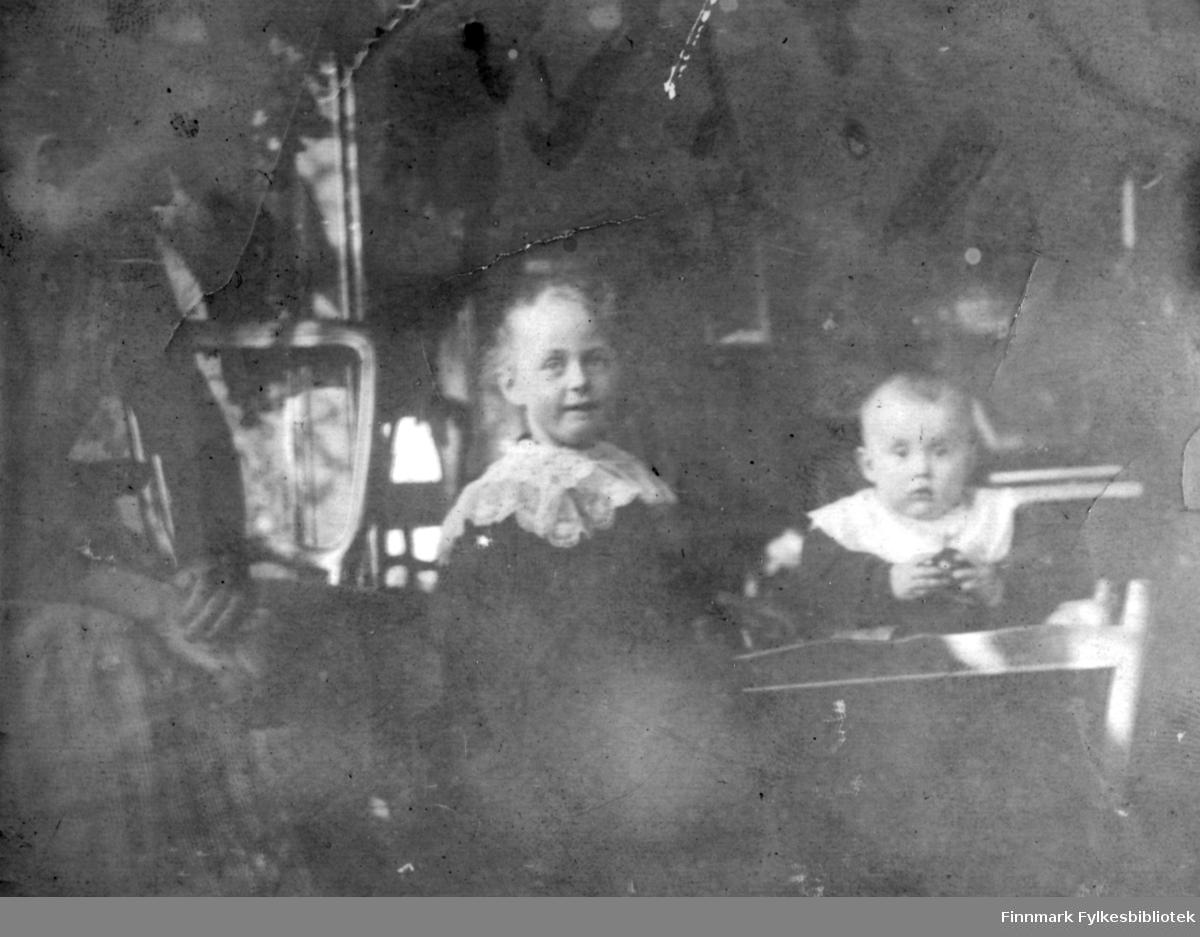 Tre personer fotografert i et rom. Til venstre sitter en dame i rutet skjørt som hviler armene sine på lårene. I midten er en ung jente i mørk kjole. Hun har et hvitt, lite sjal rundt halsen. Til høyre sitter et spedbarn. Barnet har mørk påkledning med en hvit smekk rundt halsen. Et lite bord/brett står foran barnet. I bakgrunnen ses ryggen på en stol og en lampe stående på et bord.