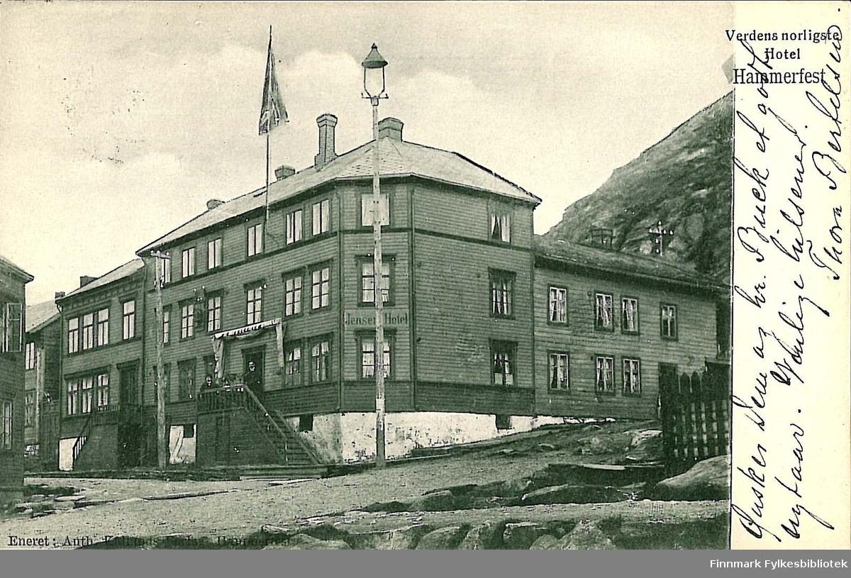 Postkort med motiv av Jensens hotell i Salsgata. Kortet er en jule- og nyttårshilsen til Arthur og Kirsten Buck på Hasvik. Kortet er sendt fra Hammerfest i desember 1903.