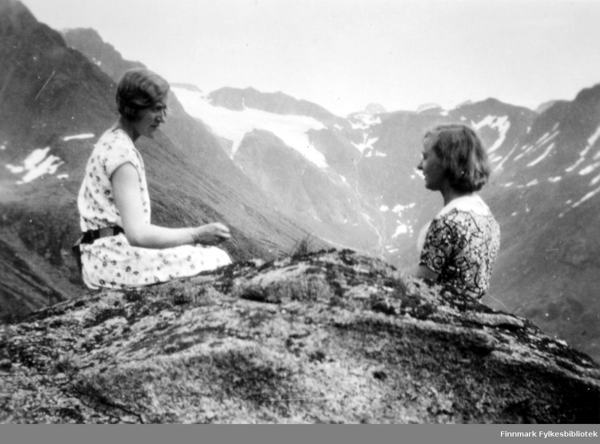 To unge damer på en fjelltopp. Begge har sommerkjoler på seg. Hun til venstre har en kortermet, lys med prikker og et sort belte rundt livet. Hun til høyre er iført en mørkere med mønster og korte ermer. Høye fjell med bratte fjellsider rundt dem. Der de sitter er det bart, men ellers er det endel snøflekker i fjellet.