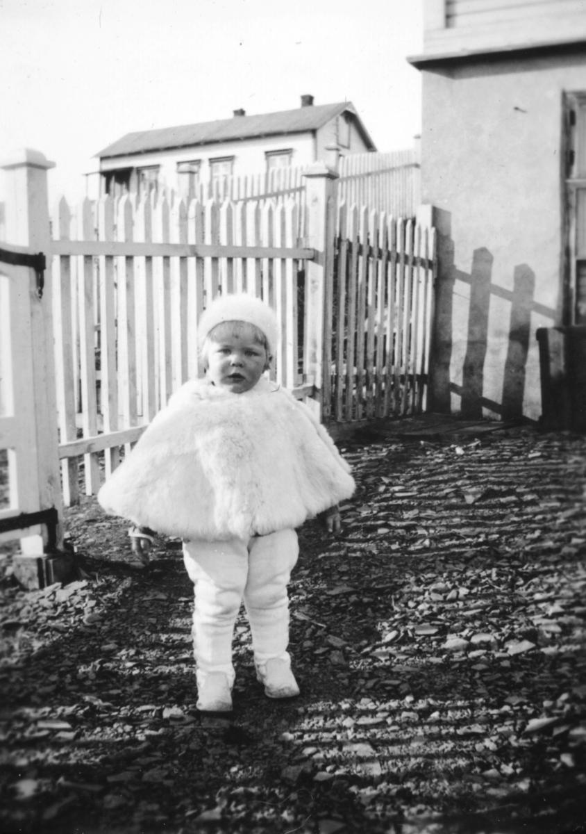 Tor Hauge i kep og full stas, i haven hos sine besteforeldre. De bodde i Nyborgveien, nå nr. 40. Ballo huset ses i bakgrunnen