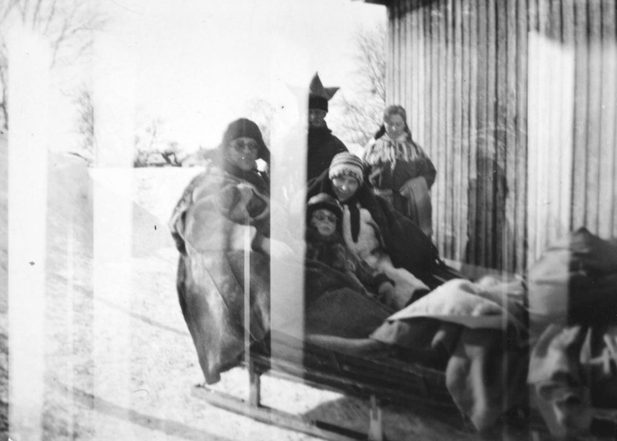 Tor Hauge og moren Alfrida Hauge som sitter i en slede. De er kledt i lånte pesker. Det sitter en ukjent mann sammen med dem i sleden, også han i pesk. Bak dem, ved husveggen, står en mann og en kvinne. De er kledt i samiske klær. Det er vinterstid, og det ligger snø på bakken