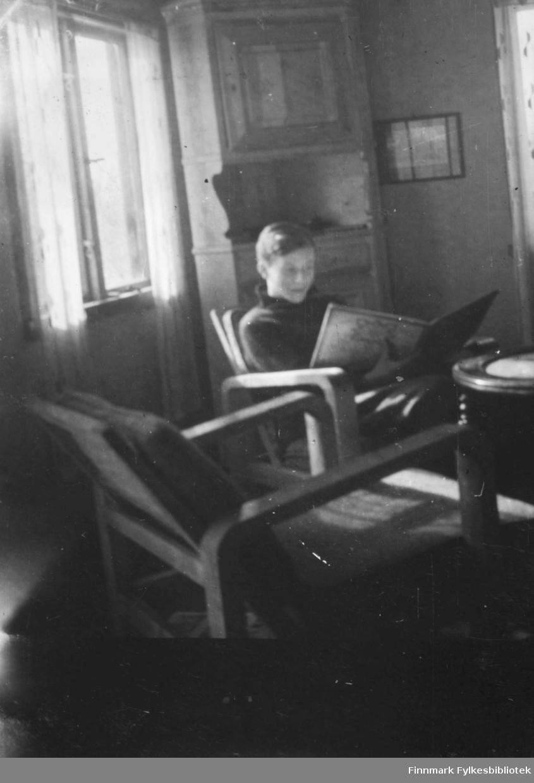 Johan Ballo og Per Bjørgan på hyttetur i Hauge hytta i Andersbyskogen Gutte leser sitter i stol inne i hytte. Per Bjørgan leser i hytta.