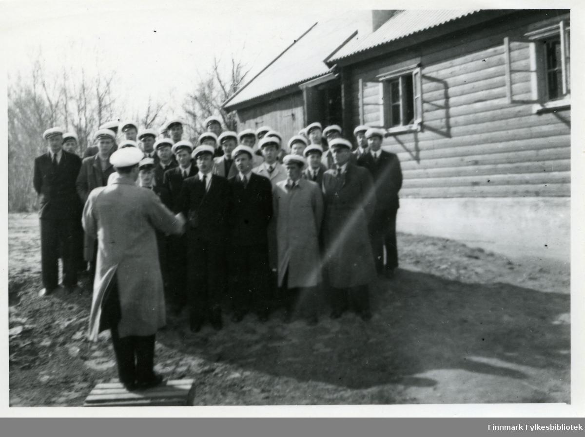 Bildet viser Vadsø mannskor utenfor Leif Johnsens hus og er tatt 19.06.1949 i Rusfjelbma. Som dirigent har koret Sæland. Alle medlemmene har på seg hvite hatter, trolig kor uniform. Alle har på seg frakker og slips. Huset i bakgrunnen har to vinduer og man kan skimte en døråpning.