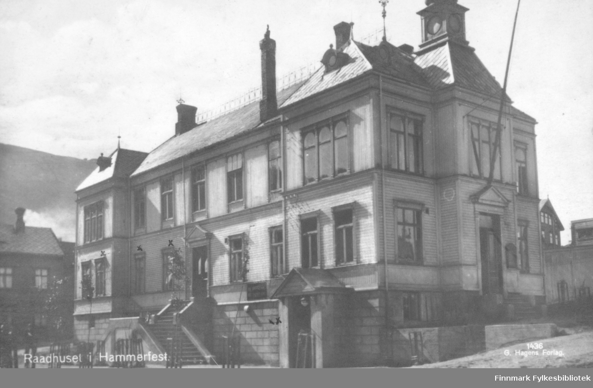 Et postkort med Rådhuset i Hammerfest som motiv. På bygget kan man se vinduer, grunnmur, tak og piper. Bygget er laget av tre. En stor flaggstang står stilt ovenfor en inngang. I bakgrunnen kan man se andre hus.