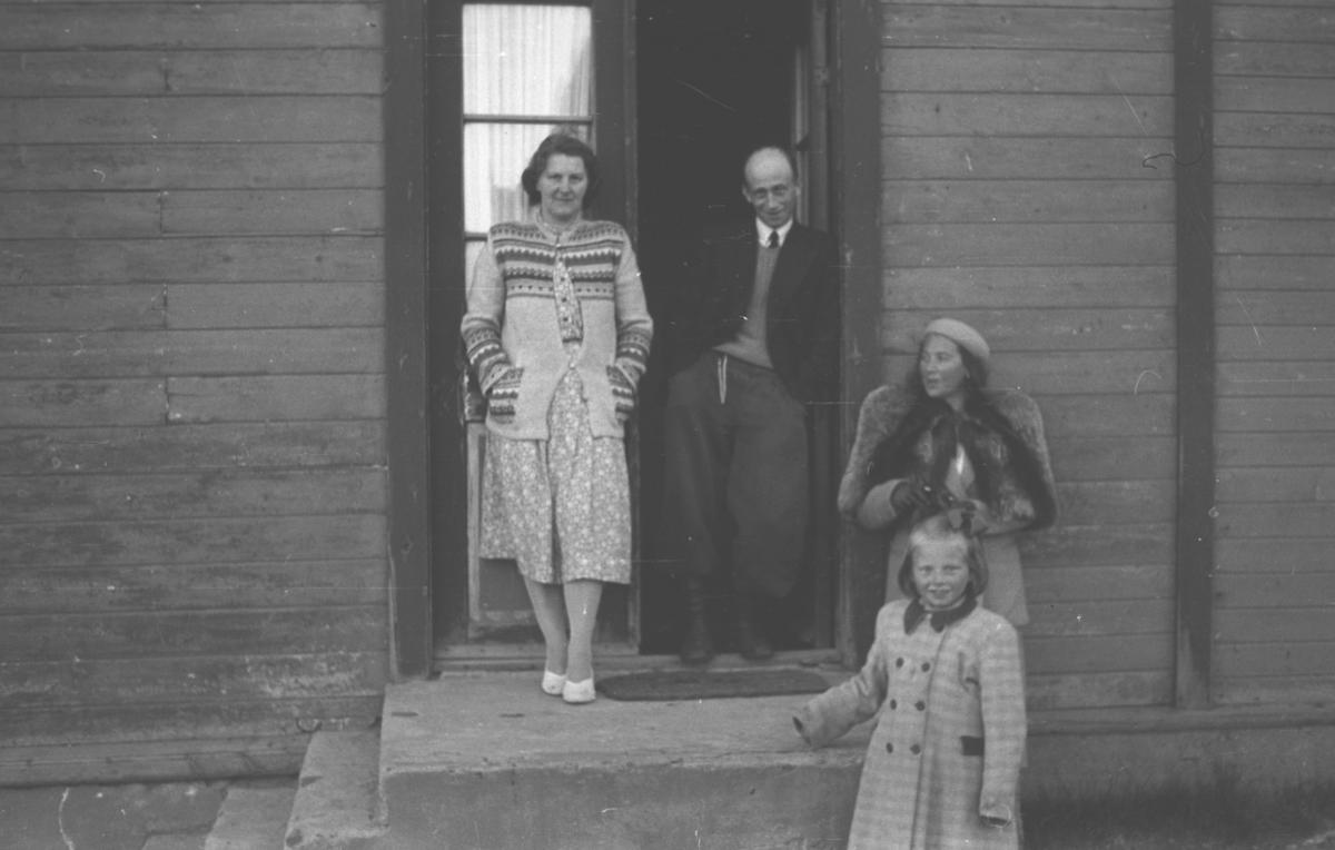 Fire personer står ved en inngangsparti til en bolig. De er, fra venstre: Rønnaug Haldorsen, Saralf Haldorsen, Frida Hauge en en jente foran Frida som heter Haldorsen (fornavn ukjent). Stedet er ukjent, men kan være i Vadsø.