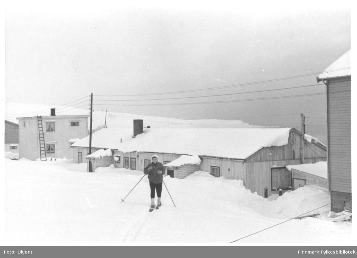 En kvinne skal på skitur rett fra søsterbrakka i Vadsø. Hun er muligens en sykepleier. På seg har hun vinterklær; lue, jakke og bukse. På bena har hun ski og hun holder på skistaver. På bygningene bak kan man se vindu og skorsteiner. En stige lener seg på bygget til venstre. Man kan se en strømlinje midt i bildet.