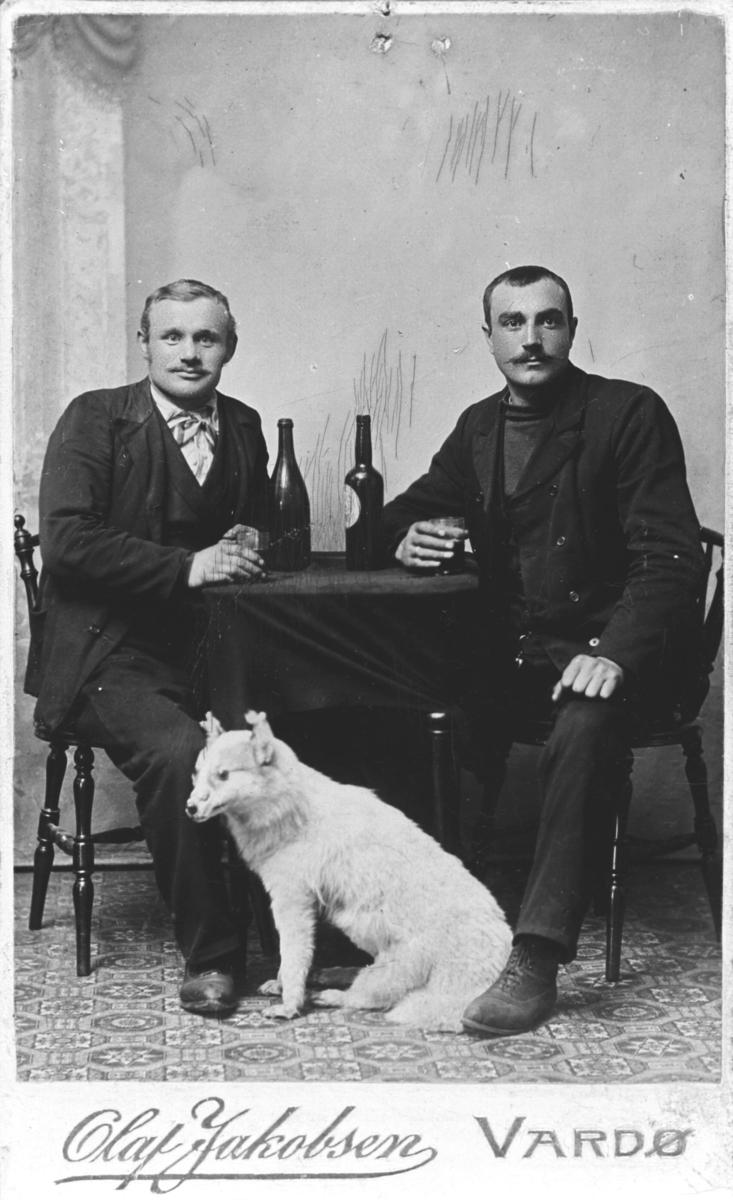 To menn, til venstre Oskar Ittelin, sitter ved bord i atelieret til Olaf Jakobsen. På bordet står to vinflasker og to glass. Bordet er dekket av en mørk duk. Mennene holder på glassene sine og ser rett på kamera. Foran dem på gulvet sitter en utstoppet rev eller et lignende dyr