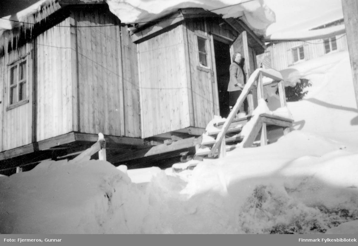 En dame står på trappa til et gjenreisningshus med mye snø på taket og i terrenget. Persoenen er ukjent.