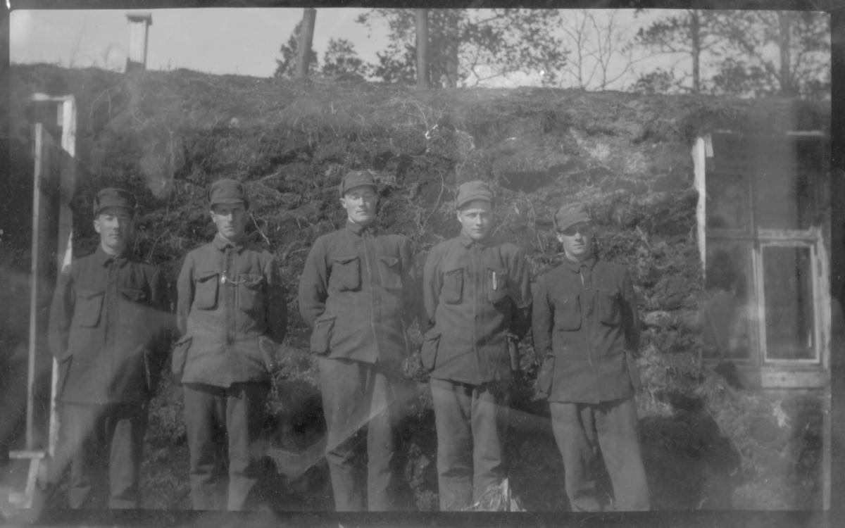 Bildet viser fem uniformerte menn som står utenfor den gamle garnisons gamma ved Svanvik, brent  i oktober 1944.