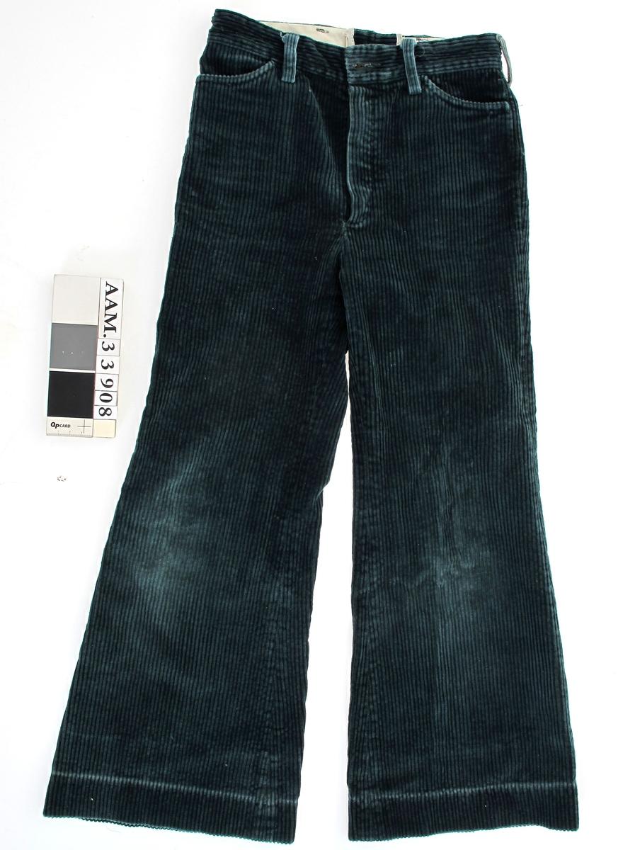 """Barnebukse i grønn cordfløyel. Med """"sleng"""" i bena. Beltestropper, 4 lommer. Oppbrett i bena er lagt ned.  Etikett fra fabrikk Berserk i Kristiansund."""