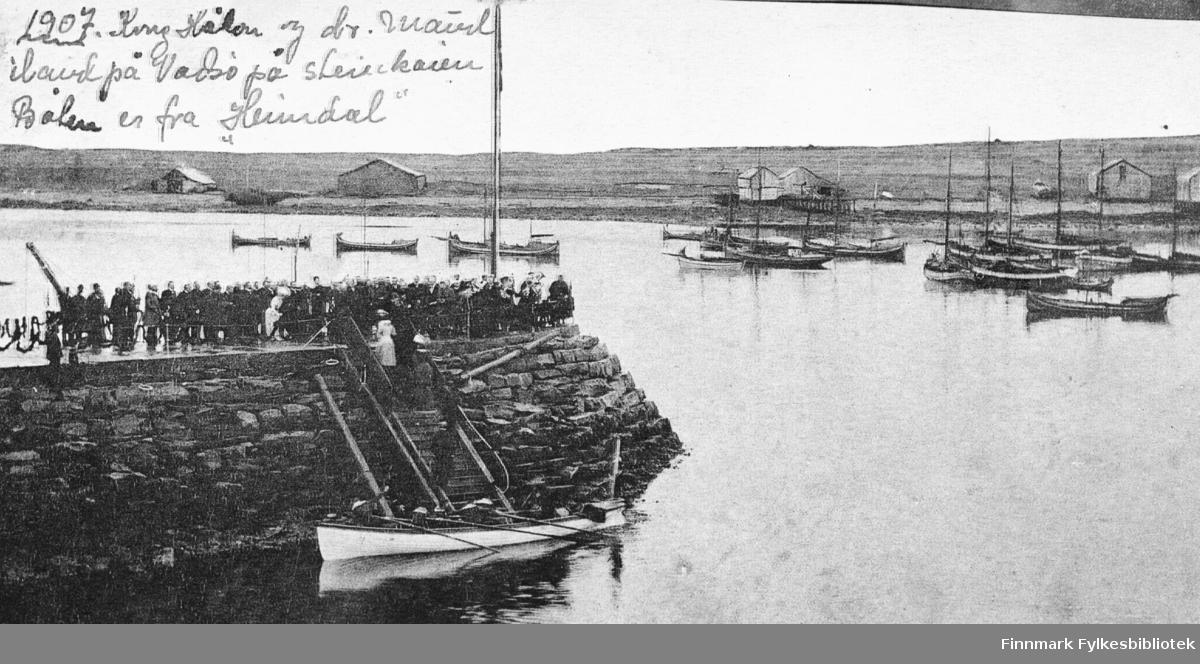 Kong Haakon VII og dronning Maud på besøk i Vadsø 1907. Kongeparet går i land ved steinkaien. På kaien står folk og tar dem mot. Ved kai ligg en stor kano som er fra 'Heimdal'. På andre sidan ved øya ligg det flere seilbåter (med seilene ned) og på land noen stabbur og andre byggninger.
