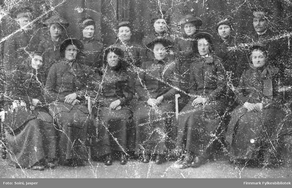 Frelsesarmeen fotografert hos J.Soini i Vadsø. 12 kvinner og to menn, seks av dem sittende i første rekke og seks stående bak. Dagny Rebekka Pedersen (g. Mietinen) er den tredje fra høyre bakerste rekke. Alle er kledd i uniform.