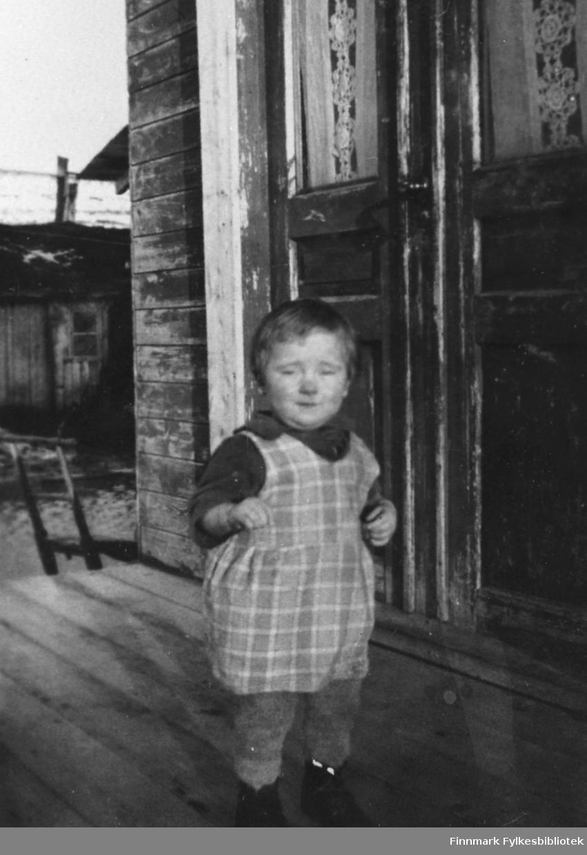 Lille Marta Mietinen fotografert på trappa tidlig på våren. Hun står ved ytterdørren og er rødkinnet (til og med nesen ser ut og være rød). Antagelig er det ennå kalt ute og jenten er kledd i kortermet skjorte, kjole og ulbukser. Hun er 1-2 år gammel på bildet.