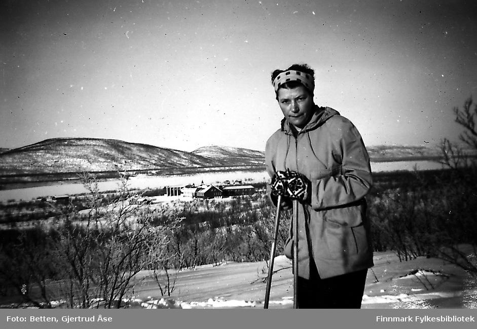 En kvinne, Hjørdis Amundsen, på skitur i Seida. Bak henne skimtes Seida internat og skole. Hjørdis jobbet som husmor på skolen i 50-tallet.
