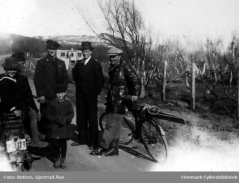 Fire menn og to gutter står på vegen.  Fra venstre:Rolf (gutt) og Magnus Betten på en motorsykkel, Einar og Nils Betten stående ved sidan av, lærer Karl Hoel lenende mot sykkelen sin og Nils Hagbart Betten (gutt) stående foran mennene.