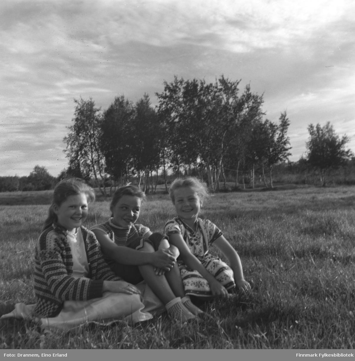 Mari-Ann Nilssen, Maija Hoikka og Turid Lillian Drannem sitter i gresset i Øvre Neiden