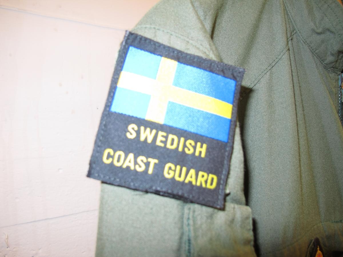 """Overall, grön med emblém. På höger ärm svensk flagga med texten """"Swedish coast guard"""" undertill.  På höger ärm Kustbevakningens örnhuvud och gradbeteckning. På höger bröst emblém: Kustbevakningen flyg. På vänter bröst rund EU-flagga och där under textband """"Kustbevakningen"""". Av bomullsmix."""