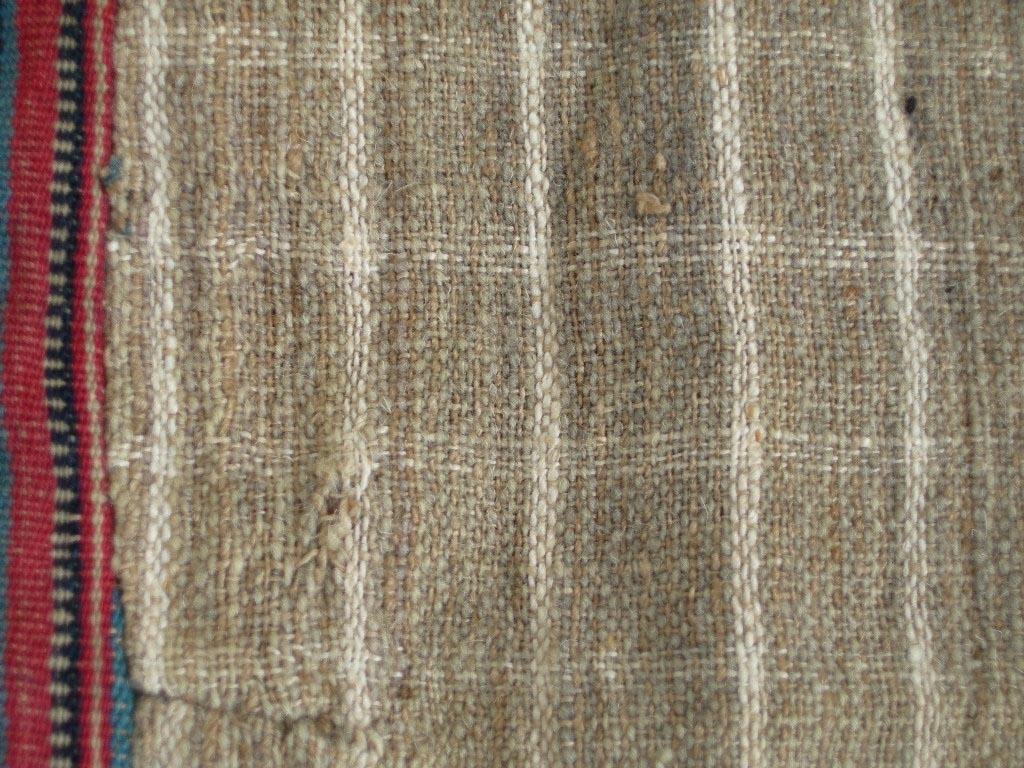 Livstycke från Toarps socken, Ås härad, Västergötland. Randigt inslagsdominerat tyg i korskypert. Varp: entrådigt oblekt lingarn. Röd botten i ullgarn med ränder vävda i ullgarn i brunt, svart, mörkgrönt med flotteringar i gult, samt vita, blå och flammfärgade vita och röda ränder i bomull. Sytt med 4 cm långt skört, kilar i sidorna och skörtflikar bak. I framkanterna är tyget skarvat flera gånger. Knäpps med 7 par hyskor och hakar, men den nedersta på höger framstycke saknas. Fodrat med tre olika tyger: I framkanterna tuskaftsvävt tyg med entrådigt oblekt lingarn i varp och inslag samt ullgarn i rött, blått, grönt, brunt och beige, mönsterränder i tvist och flotteringar. Runt axelpartierna och del av ryggen tuskaftsvävt tyg av oblekt entrådigt lingarn i varp och blått entrådigt ullgarn som inslag. Övriga delar fodrade med ett rutigt linne i blekta och oblekta garner.