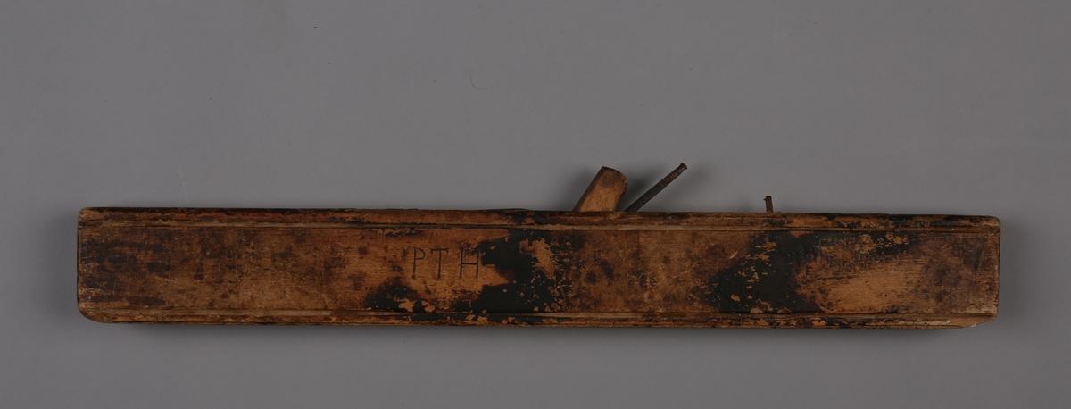 Rektangulær høvel med jernskjær og liten trekile for regulering.