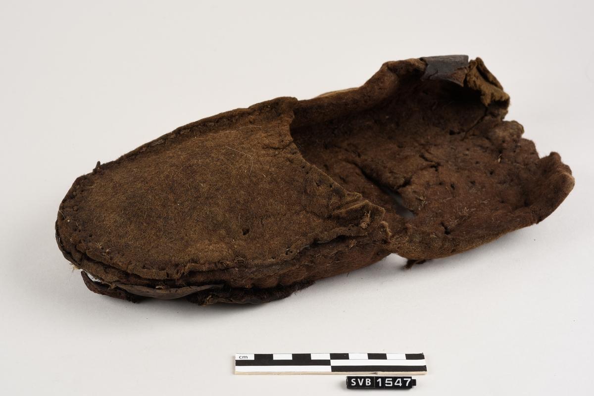 Tøffel av tovet ull med lærsåle. Deler av sålen mangler og tøffelen er uten hæl. Tøffelen er sydd sammen langs kantene. På høyre side og bak på tøffelen er det en lærreim . Tøffelen er mørk brun i farge.