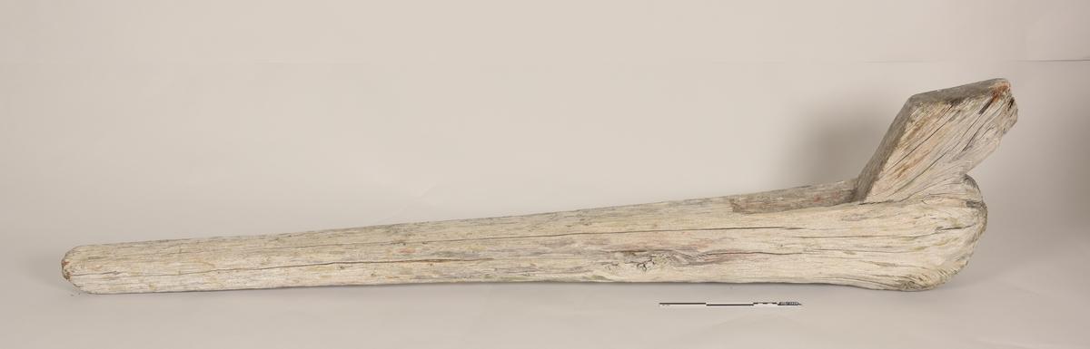 Avlang tregjenstand med rektangulært tverrsnitt. Gjenstanden smalner mot den ene enden. I den bredere enden er det en rektangulær utsparing tvers gjennom.