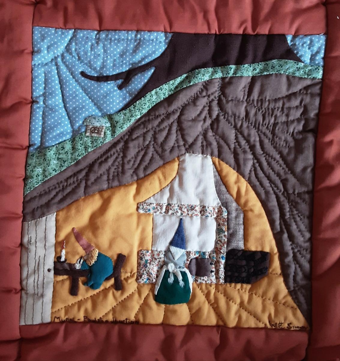"""Lappeteppet består av 20 ulike bilder. Hvert enkelt bilde er håndsydd og brodert. Det skal vise motiver fra Skandinavia og USA, gammel og moderne tid. På hver enkelt bilde er det brodert inn navnet til den som har laget det. Alle delene har så blitt montert sammen til et stort sengeteppe. Brun innramming og bakside. Vattert. Tekst på bIldemotivene fra øverst til venstre: 1. Audrey Edmonds 2. Ness Place,1901, Shirley Martinson 3. Poulsbo Junction, Renee Gustafson 4. Swedish Horse, Nancy Bauman 5. Mural-Poulsbo Junction, W.E. Simon 6. Mural - 1st. Avennue, Margaret Moriarty 7. The Mall(?), J. Bodner 8. Jensen Way, Audrey St. Clair 9. Sons of Norway 1918-1972, Bonnie Olson 10. Marcia Nelson 11. Circa 1900, Third Ave. NE, Ann Mossman 12. Viking Ship, Poulsbo Elementary, Marie Barkov 13. Irma Tweiten 14. """"1894"""" 3rd Aveny S., Kathy Holodnak 15. Telephone Blog 1935, Jensen Way, Anne Cook 16. Mural First Avenue, Mary Ann HIll 17. Viking, Olga Arne 18. 1st Lutheran 1908, ???? Freiboth 19. Velkommen til Poulsbo. Mural First Avenue. Poulsbo Quilt 1980. Artist - Annie Campbell, Coordinator - Irma Tweiten, Li Johnson 20. Viking Ship, Edna Eisses"""