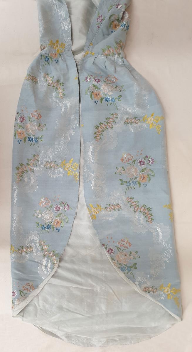 Dåpsveip av silke, med brodert blomstermotiv i flere farger over det hele på lyseblå bunn. Fôret med tynn lyseblå silke. Sveipet er omsydd etter en brudekjole.