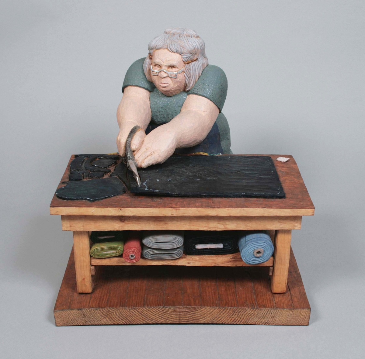 """Skuren och målad träskulptur av al och enträ. Kallad """"Tillskärerska"""". Tillverkad av Larsåke Heed i Målsryd.  """"Min skulptur """"Tillskärerska"""" är skuren ur ett stycke alträ. Saxens skänklar gjorde jag av ene. Tillskärarbordet är gjort i en över- och underdel, också al, som sammafogats med benen och dess tvärgående regel. Överdelen med det tillskurna tyget, måttbandet och kritan är alltså en träbit och hyllan med tygrullarna består av en bit.  På 1950-talet, efter avslutad folkskola, började jag arbeta inom konfektionsindustrin. Min """"Tillskärerska"""" kan väl sägas vara ett minnesfragment från den tiden. Kvinnan har ingen förebild i verkligheten, utan är en sammanställning av olika intryck. Min mor Ella Heed, som var  privatsömmerska, hade ett liknande bord i sitt arbetsrum. Hon sydde företrädesvis klänningar, var nogrann och kunnig i att få en bra passform på  kläderna, även om beställarna oftast var långt ifrån några mannekängtyper. I kundkretsen ingick en del """"finare"""" damer, (andra hade väl sällan tid och råd) som anlände i blänkande """"mercor"""", med uniformerade privatchaufförer, som bar väskor med tyger och modejournaler.  På fabrikerna såg man både manliga och kvinnliga tillskärare. Ofta var de specialiserade på en produkt, exempelvis skjortor, byxor eller jackor. Männen hade för det mesta en så kallad svalrock, som skyddsklädsel. Alternativet var att vika en stuvbit dubbel och knyta om midjan med ett  band, som ett förkläde, vilket i regel kvinnorna gjorde. Det syntes som om man utvecklade ett revir kring sitt område, med bord, redskap, maskiner,  mönster o.s.v. Trägolven blev nötta av fötters trampande på samma ytor genom åren, så att de hårdare kvistarna stack upp som bulor ur brädorna. Unika kulturer växte fram på varje arbetsplats beträffande vanor och beteenden, alltifrån var man hade för vana att ställa sin cykel på måndagsmorgonen, eller var man brukade knacka ur sin pipa, till vitsigheterna vid frukostrasten på lördagen, inför förväntningarna på den kommande hel"""