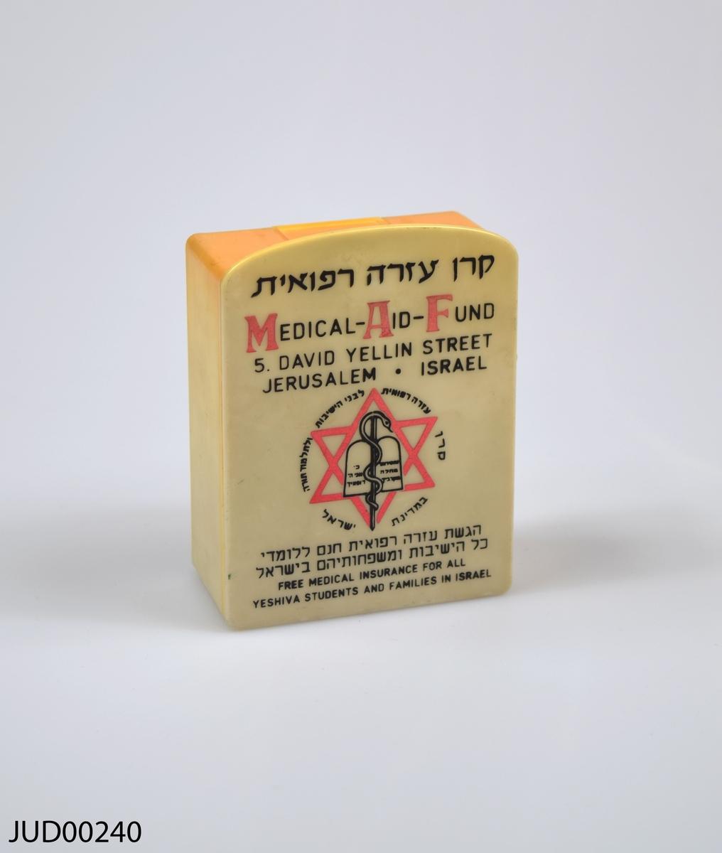Insamlingsbössa, tillverkad av vit plast. Dekorerad med röd och svart hebreisk och engelsk text, en davidsstjärna, em orm samt bild på de tio budorden.