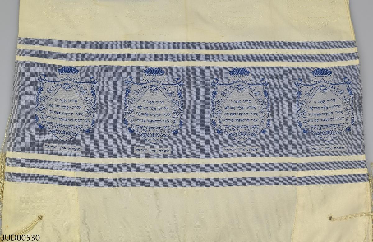 Bönesjal, troligtvis tillverkad av maskintillverkad satin. Invävd dekor i form av blå ränder med infällda sköldar i vilka hebreisk text är skriven. Likdana sköldar i vitt på det vita. I ena kanten finns ett band med hebreisk text.