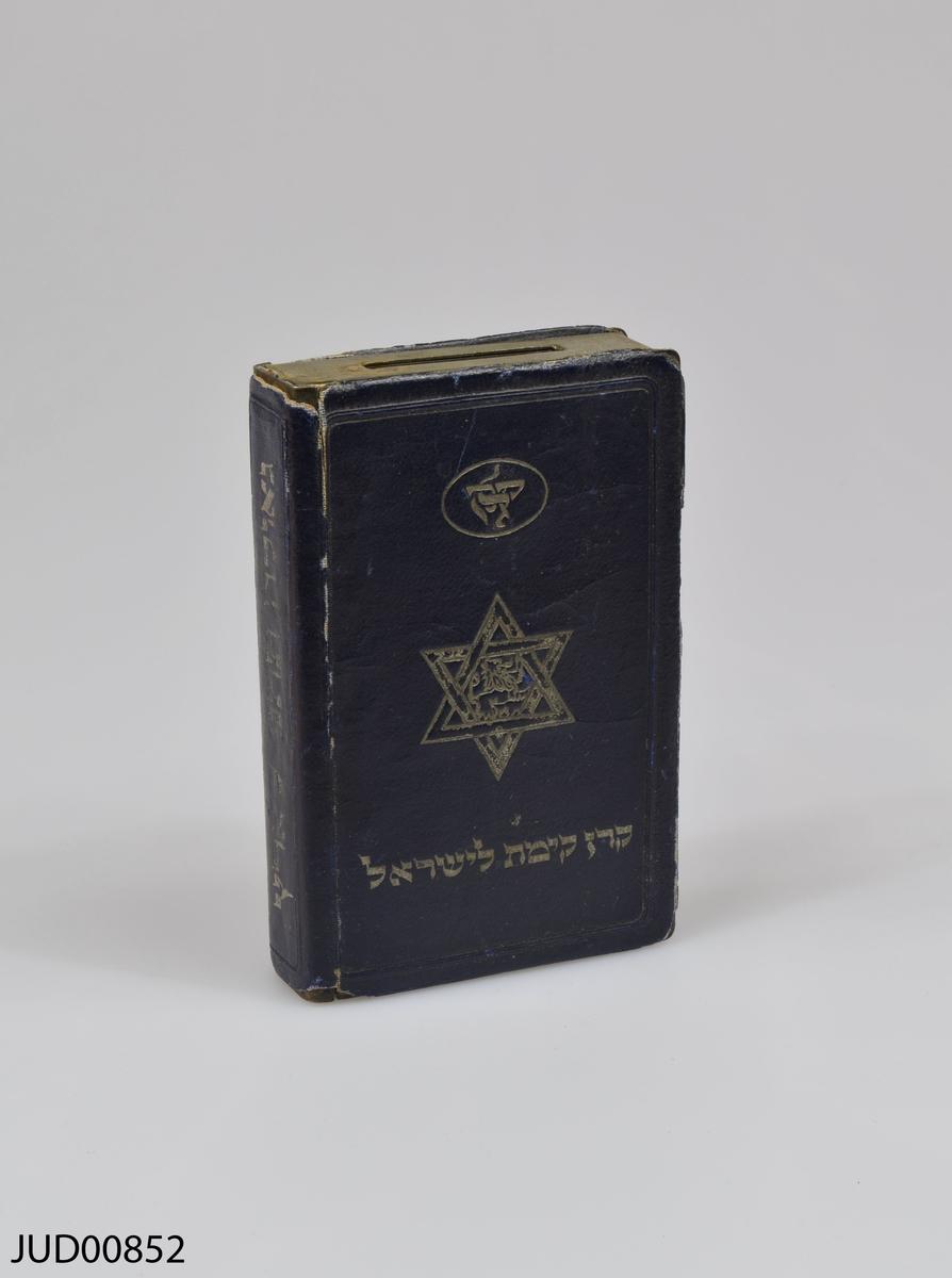 Insamlingsbössa, tillverkad av metall, i form av en bok. Hebreisk text på fram- och baksida. Karta över Israel i relief på framsidan, och en davidsstjärna på baksidan.