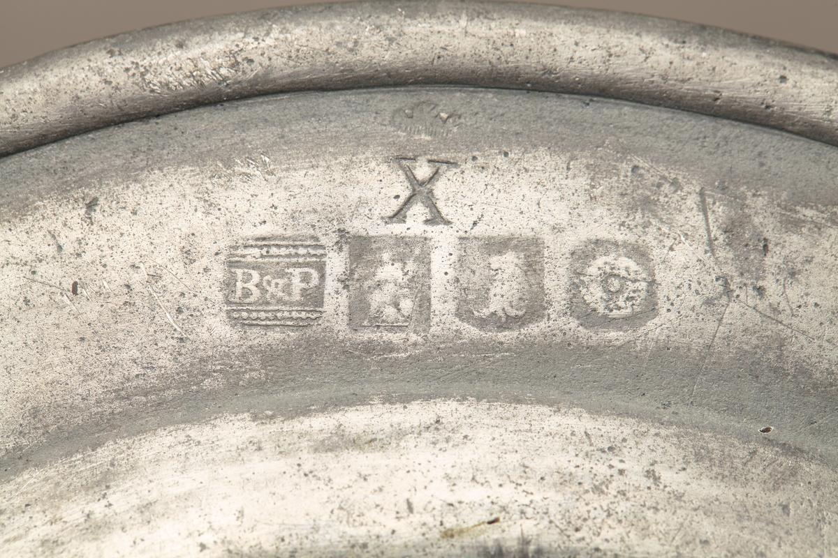 """Tinntallerken laget i London. Det er i alt seks stempler; B & P, en gud/ gudinne, et dyr, et hjul og X på den ene siden. På den andre siden London. """"4-stemplet tinn"""" lødighetsmerke av en krone X som kom etter 1700."""