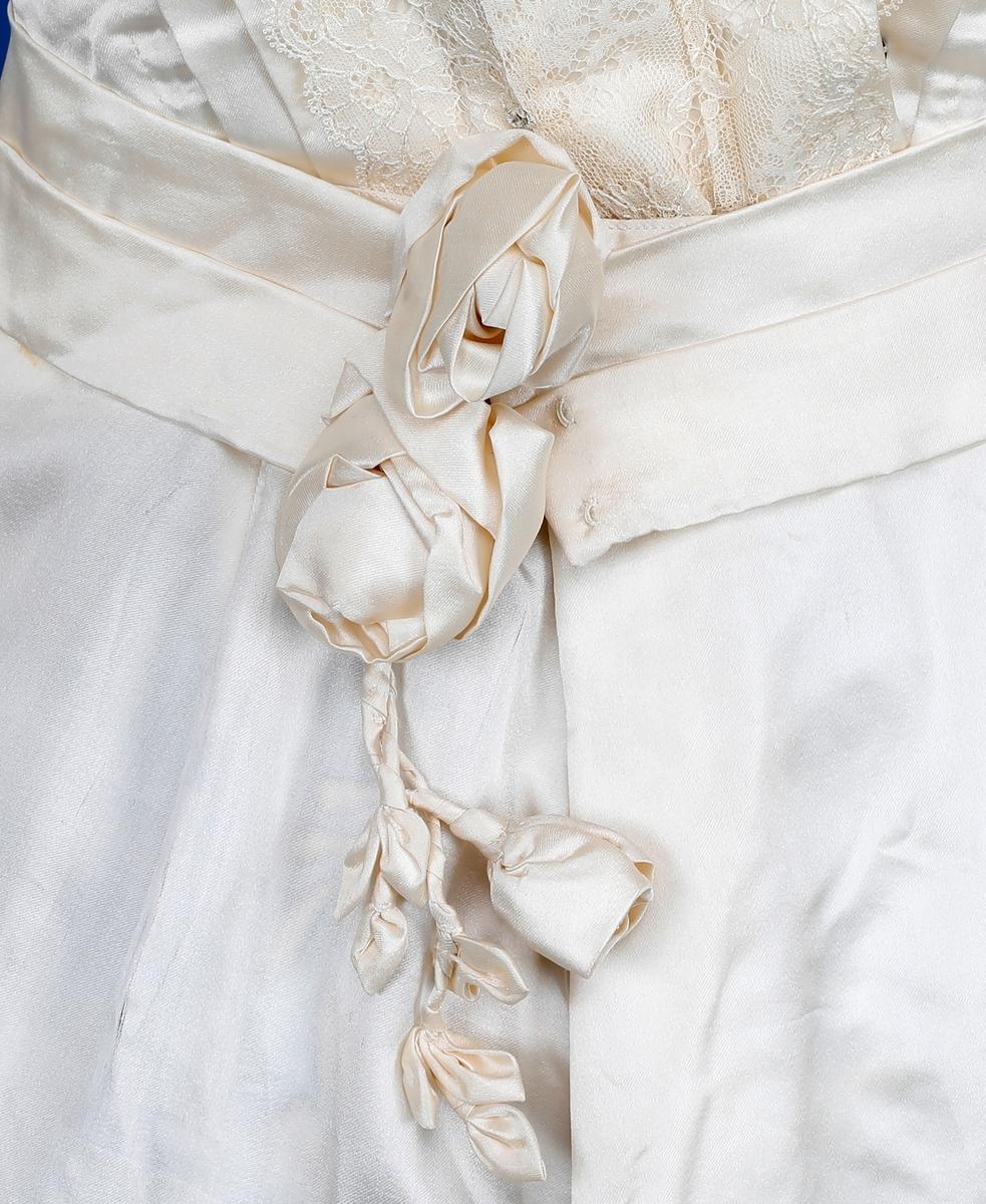 Todelt brudekjole med belte, bukettholder, hansker, slør og myrtekrans formet som hjerte. Livet har trekvart ermer. Pyntet med brede blonder på bryst og rygg som en V, og med blonder og tredimensjonale silkeblomster på ermene. Høy hals og bryststykke i gjennomsiktig materiale. Kragen er stivet opp. Lukking bak med trykknapper og hekter. Bakpå livet er det en hekte til å feste skjørtet i. Skjørtet har langt slep fòret med bomull og kantet på innsiden med foldet blonde som er stivet. Ca 30 cm opp fra nedkanten er skjørt og slep pyntet med tredimesjonale silkeblomster, stengler og blader. som er påsydd for hånd. Skjørtet er festet bak i linningen med hekter og splitten festet sammen med trykknapper. Bakpå skjørtet er det en øyehekte til å feste i skjørtet. Beltet festes foran under to tredimesjonale silkeblomster med tre hekter. Ned fra blomstene henger det stengel med en blomsterknopp og blader. Brudebukettholder av papir og silke (stiv) er pyntet med tyll rundt kanten og med hengene tyll. Sløret er klumpet sammen, men ser ut til å ha vært langt. Hansker av tynt, hvitt skinn. med splitt og knepping med tre knapper ved håndleddet. Myrtekransen er formet som et hjerte. Den er veldig skjør.